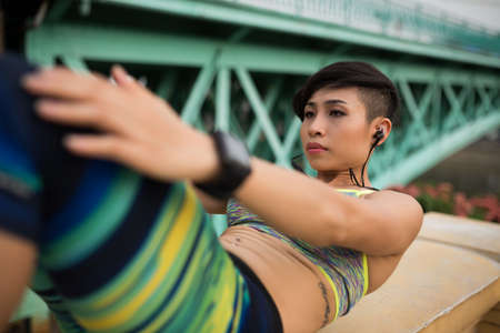 Concentrated young Asian girl doing sit-ups outdoors Stock Photo