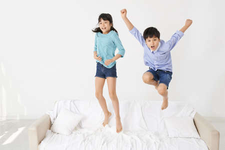 twin bed: Joyful mixed-raced twins jumping on the bed