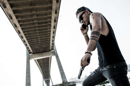 Gangster with gun taking on the phone outdoors Stock Photo