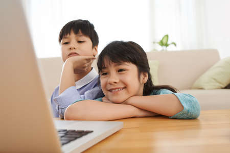 Twins watching something on laptop at home