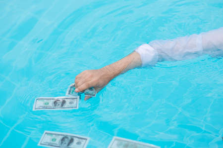 Hand of businessman trying to catch wet banknotes in the water Stock Photo