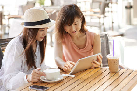 Cheerful Asian girl showing something on digital tablet to her friend Stock Photo