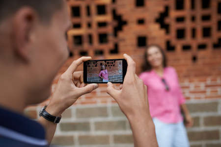 Man taking photo of his wife standing at the brick wall
