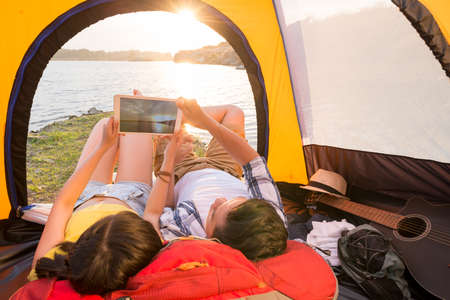 Campers taking photo of sunset on digital tablet