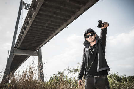 Bad guy pointing his gun outdoors
