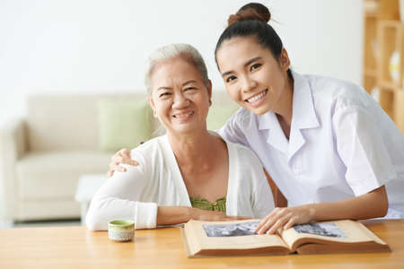 Young nurse taking care of aged female in clinic