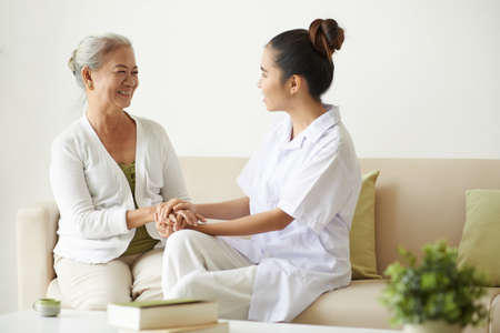 Young nurse supporting elderly woman Stock Photo