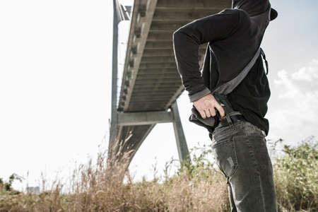 Man hiding his gun in his jeans Stock Photo