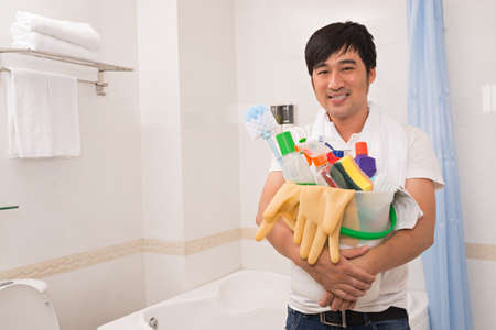 desinfectante: Smiling Asian guy with basket of cleaning supplies standing in bathroom Foto de archivo