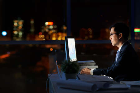 Financial manager working alone in dark office