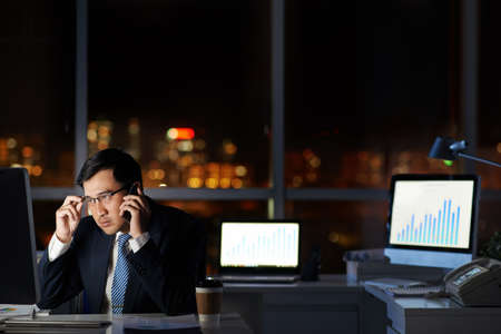 Asian business executive talking on the phone and checking information on his computer