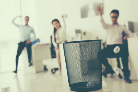 Coworkers throwing crumpled paper into waste basket, selective focus