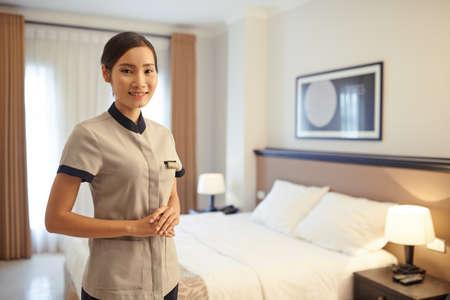 Portrait of smiling Vietnamese chambermaid in tidy room Фото со стока