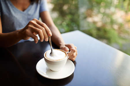 Woman mixing sugar in cappuccino with a spoon Stock Photo