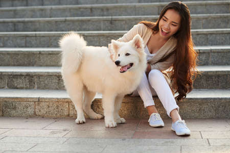 Cheerful Asian woman playing with her American Eskimo dog