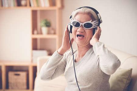 Oudere vrouw in grappige zonnebril en hoofdtelefoon zingen een liedje