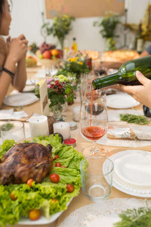 Person filling glass with red wine at party table Stock Photo