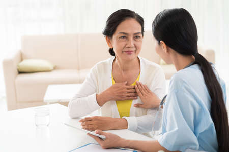 Huisarts en haar bejaarde patiënt praten over hart-en vaatziekten Stockfoto