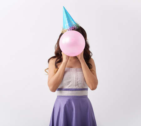 Girl in party hat blowing up pink balloon
