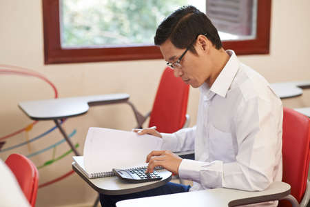 Vietnamese adult student making calculations in the class Stock Photo