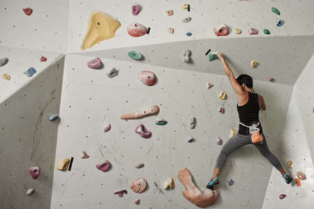 Rear view of woman practicing climbing in a gym Stock Photo