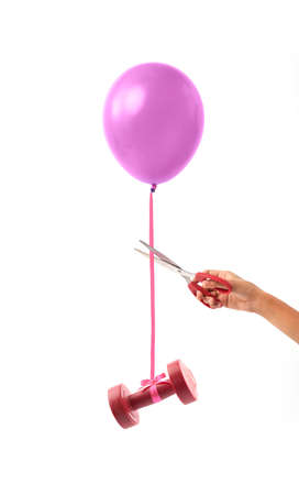 Female hand cutting lace that is tying dumbbell and balloon