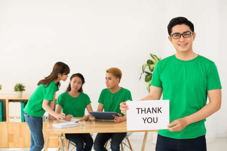 Smiling Vietnamese volunteer showing thank you board