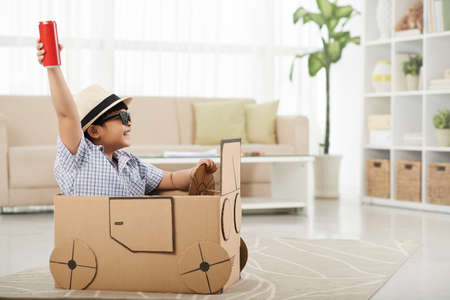raising cans: Child enjoying playing with his cardboard car Stock Photo