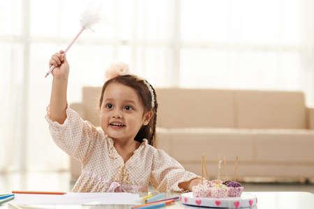 Mädchen, die vorgibt, Hexerei mit ihrem Stift zu üben