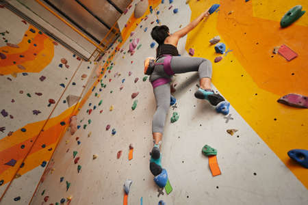 Sporty woman trying indoor climbing, view from below