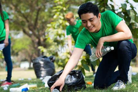 Junger Freiwilliger, der Plastikflaschen im Park aufhebt