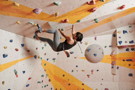 Sporty Vietnamese woman  practicing indoor climbing Stock Photo