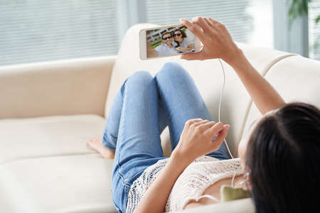couple on couch: Young woman lying on the sofa when having video call with her friends