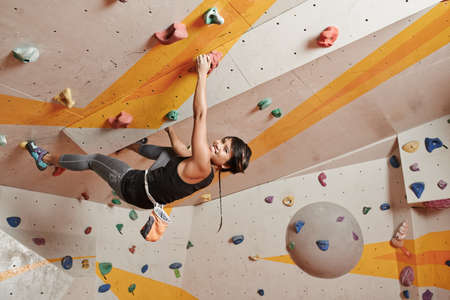 Fearless young woman climbing in sports gym Stock Photo - 76859786