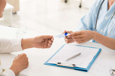 Hands of doctor giving health insurance card to senior patient