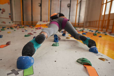 Woman climbing up rock wall in gym, view from below