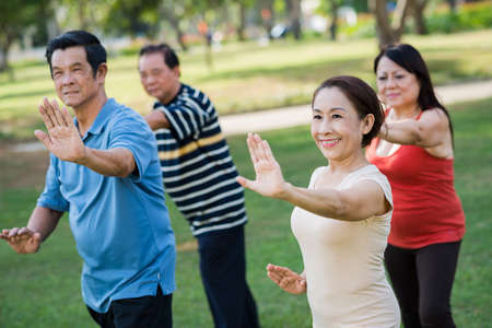 Vietnamese senior people exercising together in the park