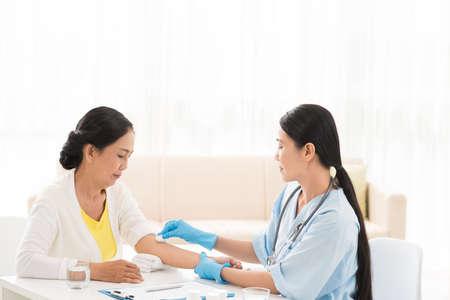 Vietnamese hogere vrouw die injectie in het ziekenhuis ontvangt