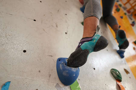 Foot of female climber on artificial boulder