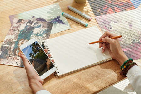 Artist copying picture from his smartphone Stock Photo