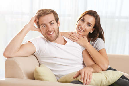 couple on couch: Portrait of young couple sitting on the sofa  and looking at camera Stock Photo