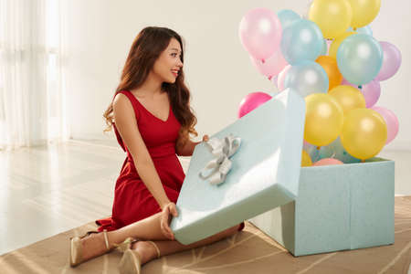 Cheerful beautiful woman opening gift box full of balloons