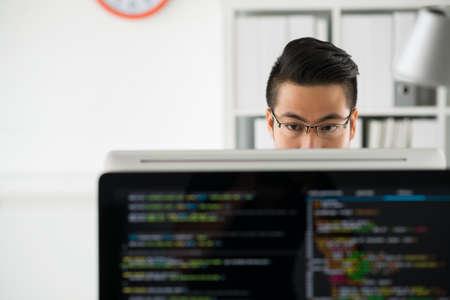 オフィスのコンピューターで作業して物思いにふけるプログラマ 写真素材