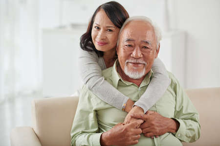 couple on couch: Happy smiling aged woman hugging her husband from behind