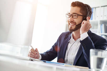 Glimlachende zakenman die hoofdtelefoon met behulp van wanneer het spreken aan klant