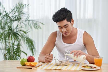 adding: Smiling young man adding milk in his granola