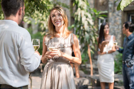 Pretty woman talking with male guest at the party Stock Photo