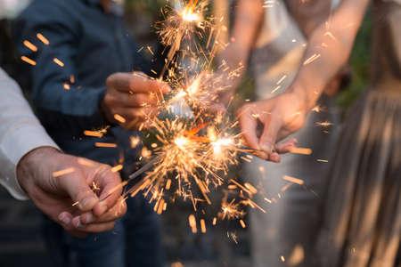 Mains de personnes tenant la lumière du Bengale à la fête