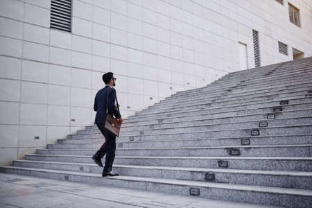 Business executive with briefcase going up the stairs Stock Photo