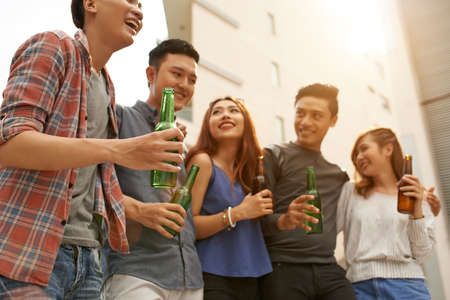 happy asian people: Group of Vietnamese young people drinking beer and chatting outdoors